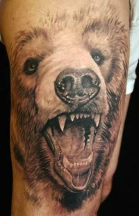 Realistic head of brown bear tattoo